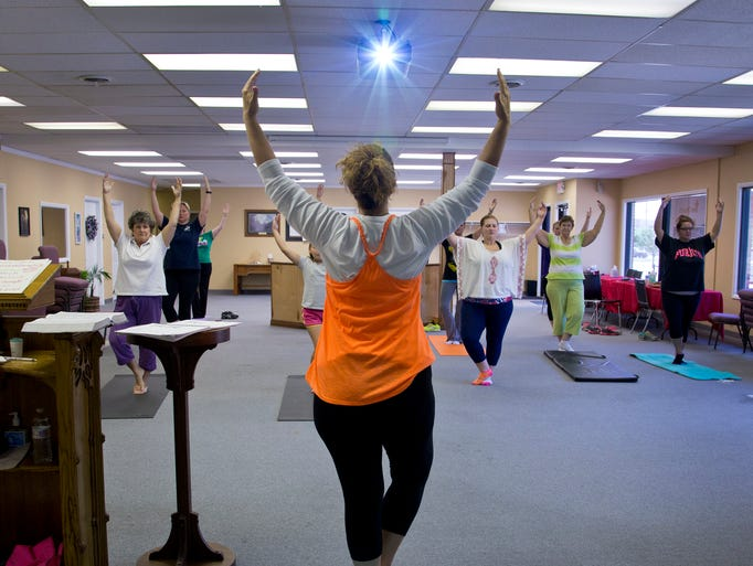 Instructor Tammy Douglas, back to camera, leads during a PraiseMoves class Saturday, July 19, 2014, at The Church in Lafayette. PraiseMoves has been labeled as the Christian alternative to Yoga where scriptures are read and praying is done.