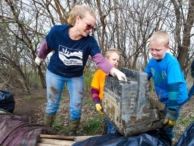 Annie Hause and her two sons, Brody, 7, middle, and Austin, 10, of Mooresville, work together to toss an old television onto a pile of debris collected along the banks of the river. Citizens Energy Group held its 26th Annual White River Cleanup. Citizens Energy Group, Friends of the White River, the Indianapolis Department of Public Works, and United Water teamed up in the effort targeted at removing trash from the banks of the White River.