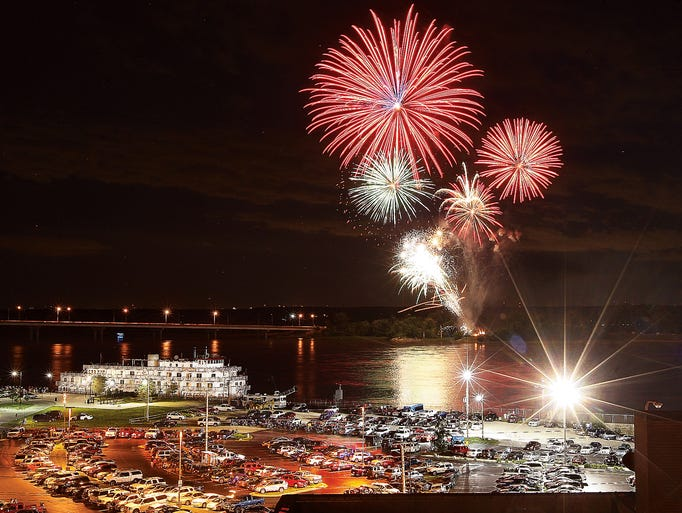 Fireworks explode over the Mississippi River on the Alton, Ill., Riverfront Thursday night, July 3, 2014, dwarfing the four-deck high Queen of the Mississippi excursion boat, left, which docked on the riverfront just before the show.