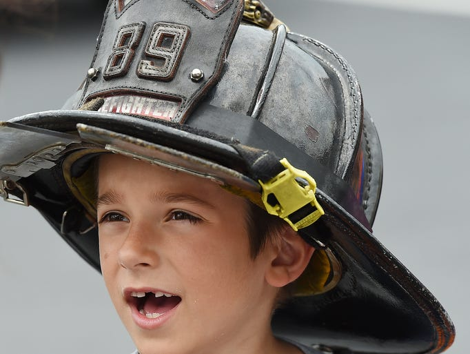 """7 year old Samuel Blake from Annapolis, MD tries on a firefighter helmet as """"Safe Kids Day"""" was held in the Lowe's Parking Lot at the store near Lewes on Saturday June 21st with Fire, EMS and Health Care groups on hand to give out information and show off some equipment and Public Safety Helicopters."""