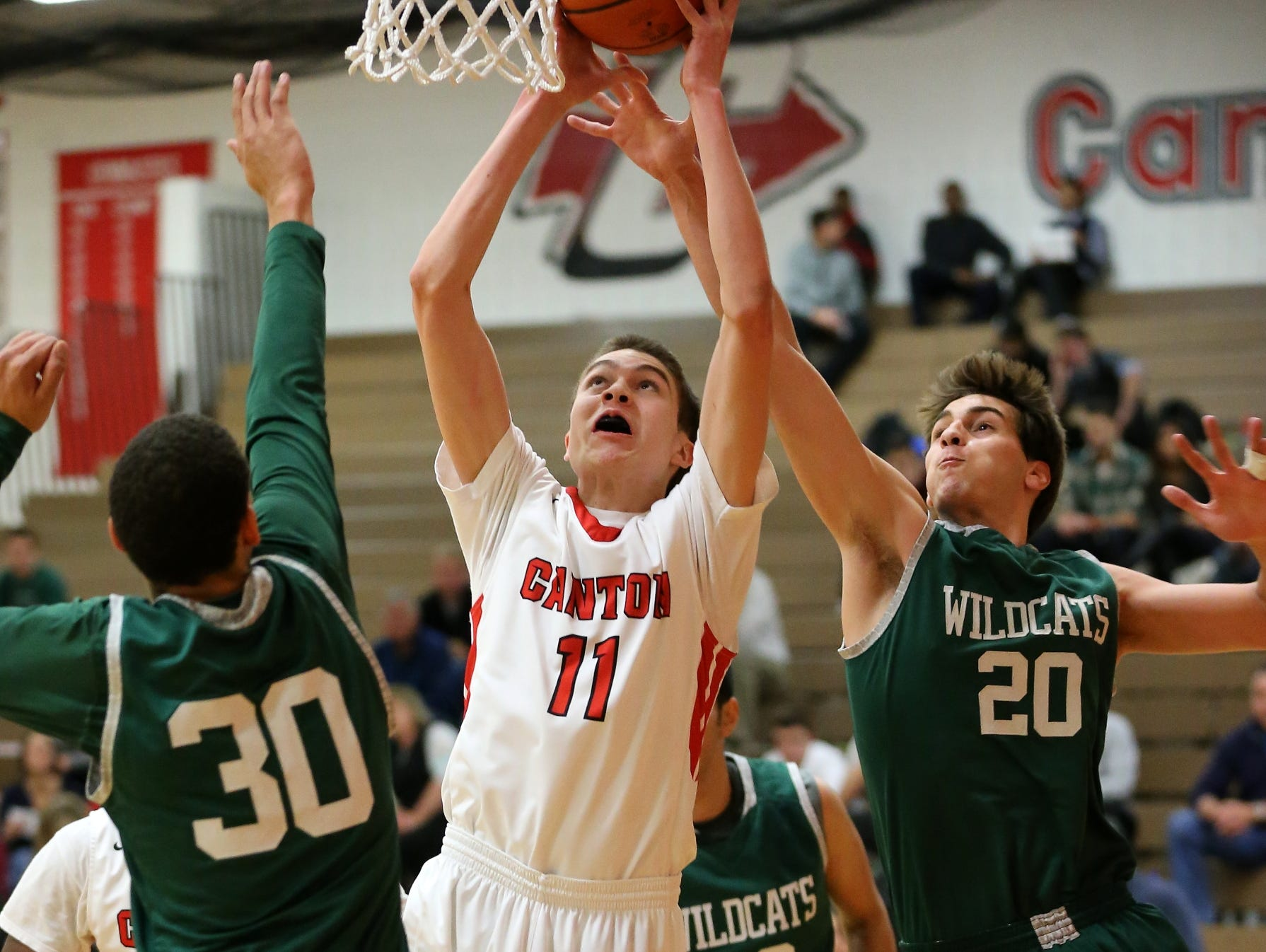Canton's Logan Ryan (No. 11) goes up for a bucket while Novi's Jay Duarte (No. 20) tries to catch up to him in time.