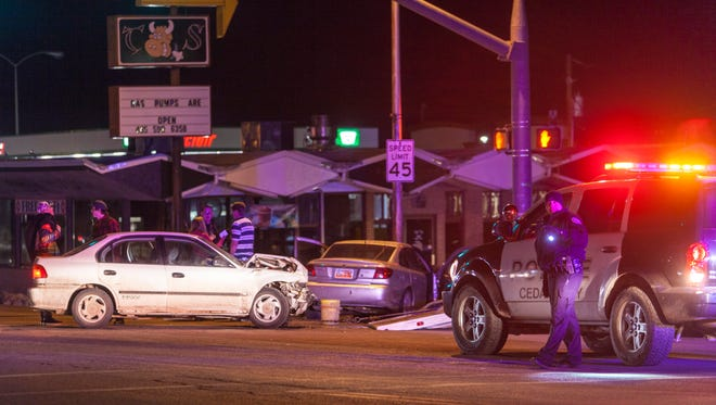 A police officer directs traffic around two vehicles involved in a wreck Wednesday night at the intersection of Main St. and 600 S., Feb. 11, 2016.