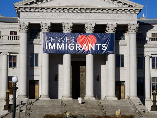 A banner welcoming immigrants hangs on the front of