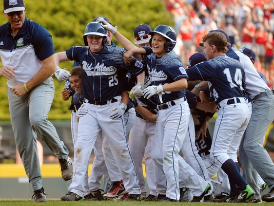 Red Land's Chayton Krauss (25) is surrounded by his teammates after hitting the walk-off run Saturday, Aug. 29, 2015, after the Little League World Series U.S. championship game featuring Red Land Little League of Pennsylvania and Pearland West Little League of Texas, in South Williamsport. Red Land defeated Pearland 3-2 in a walk-off victory to move on to the world championship game against Tokyo Kitasuna of Japan. Chris Dunn Ñ Daily Record/Sunday News