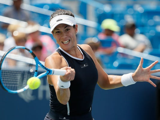 Garbine Muguruza, of Spain, returns to Madison Keys during the round of 16 at the Western & Southern Open tennis tournament, Thursday, Aug. 17, 2017, in Mason, Ohio. (AP Photo/John Minchillo)