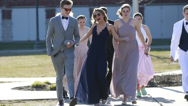 A student strikes a pose while her classmates walk along with her to the Wausau East High School 2018 prom celebration on Saturday, April 28, 2018.