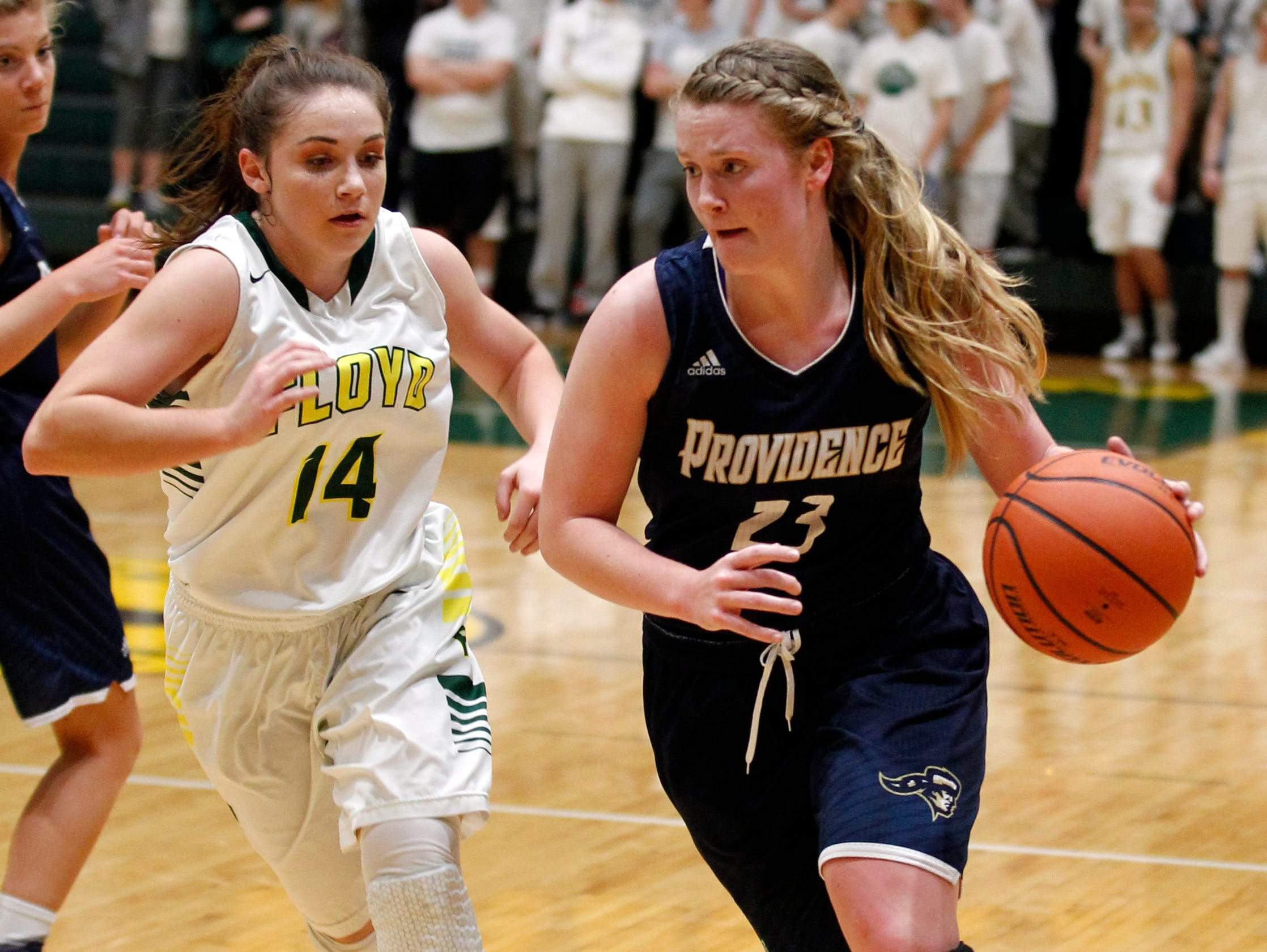 Providence High School's Claire Rauck (23) fights pressure from Floyd Central High School's Lois Endris (14) during the first half of play at Floyd Central High School in Floyds Knobs, Indiana. January 26, 2017