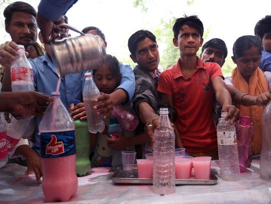 Indian volunteers offer sweet drinks to people observing