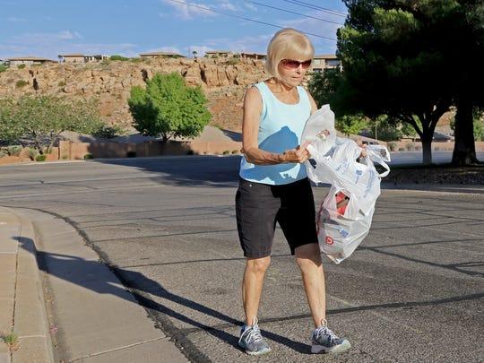 Linda Goduto picks up litter Tuesday morning near the