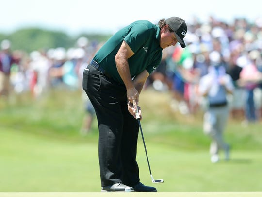 Phil Mickelson putts the fifth green during the third
