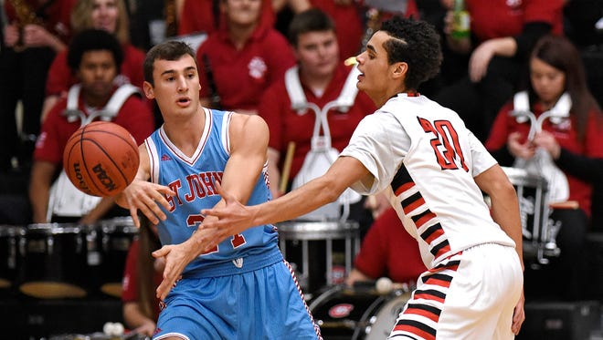 Brent Hentges of St. John's University tries to get a pass past Gage Davis of St. Cloud State University during the first half of Friday's game at Halenbeck Hall.