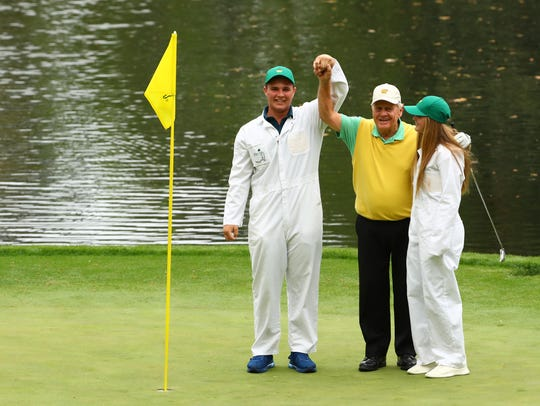 G.T. Nicklaus, the grandson of Jack Nicklaus, holds up the ball after making a hole-in-one on the 9th hole during the Par 3 Contest before the Masters golf tournament at Augusta National Golf Club.