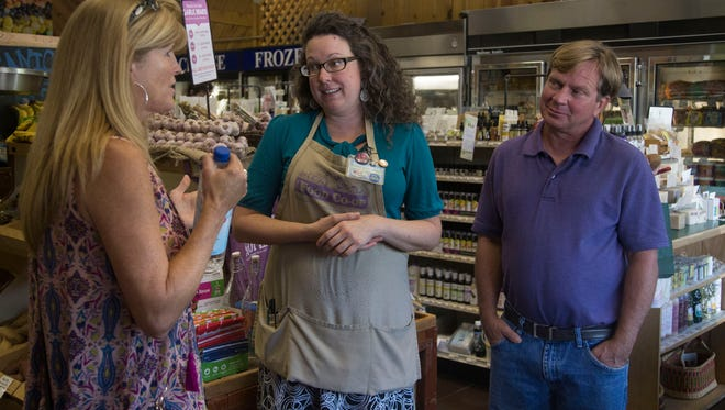 Stephanie Bublitz, center, talks with Angie Robinson, left, and John Emery, right, about potential new products Friday at the Fort Collins Food Co-op in Old Town Fort Collins.