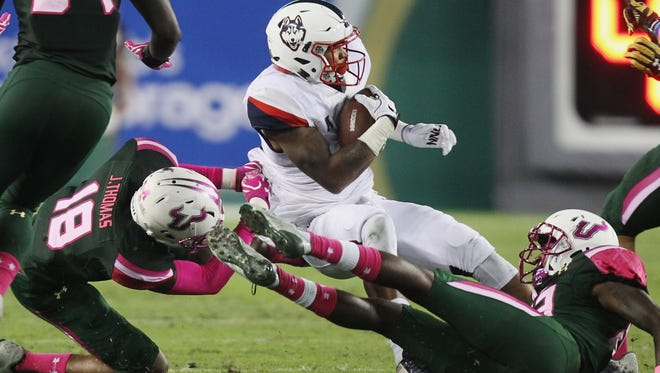 Connecticut running back Arkeel Newsome (22) is tackled by South Florida safety Jaymon Thomas (18) in the second quarter of an NCAA college football game in Tampa, Fla., Saturday, Oct. 15, 2016.