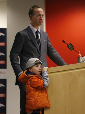 Denver Broncos quarterback Peyton Manning's son, Marshall, stands by his father during a press conference.