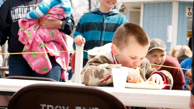 Six-year-old Judah Nason, of Athens, Pennsylvania, sloppily shoves a pancake into his mouth with his hands during the Endless Mountain Maple Festival pancake eating contest in Troy, Pennsylvania, Saturday. From left, his mother, Mary Nason, 10-month-old sister, Lydia, cousin Jacob Snyder, 12, and brother Caleb, 9, laugh and encourage him from behind a yellow rope.