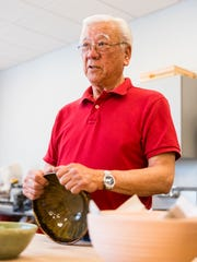Roy Kaneshiki shows off a completed bowl at Clay College