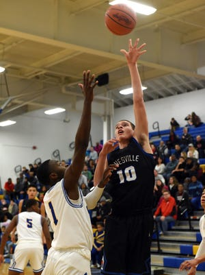 Zanesville's Kaleb Young shoots over Elijah Thomas during the Blue Devils' 80-63 loss on Saturday to host Gahanna Lincoln.