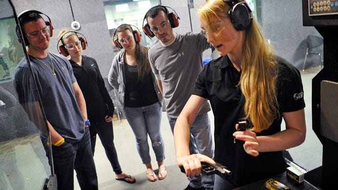 Instructors like Brooke Helm, right, are seeing more and more women coming into the Nashville Armory wanting to learn about guns and shooting. Here she is instructing Chris Stanton, Maura Reilly, tar Tulowiecke and Mike Rondenelli who were visiting from New York. Thursday April 2, 2015, in Nashville, Tenn.