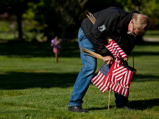 American Legion Post 449 member Robert Uyttenhove, of Forester Township, places a flag at the grave of a veteran at Riverlawn Cemetery in Marysville.