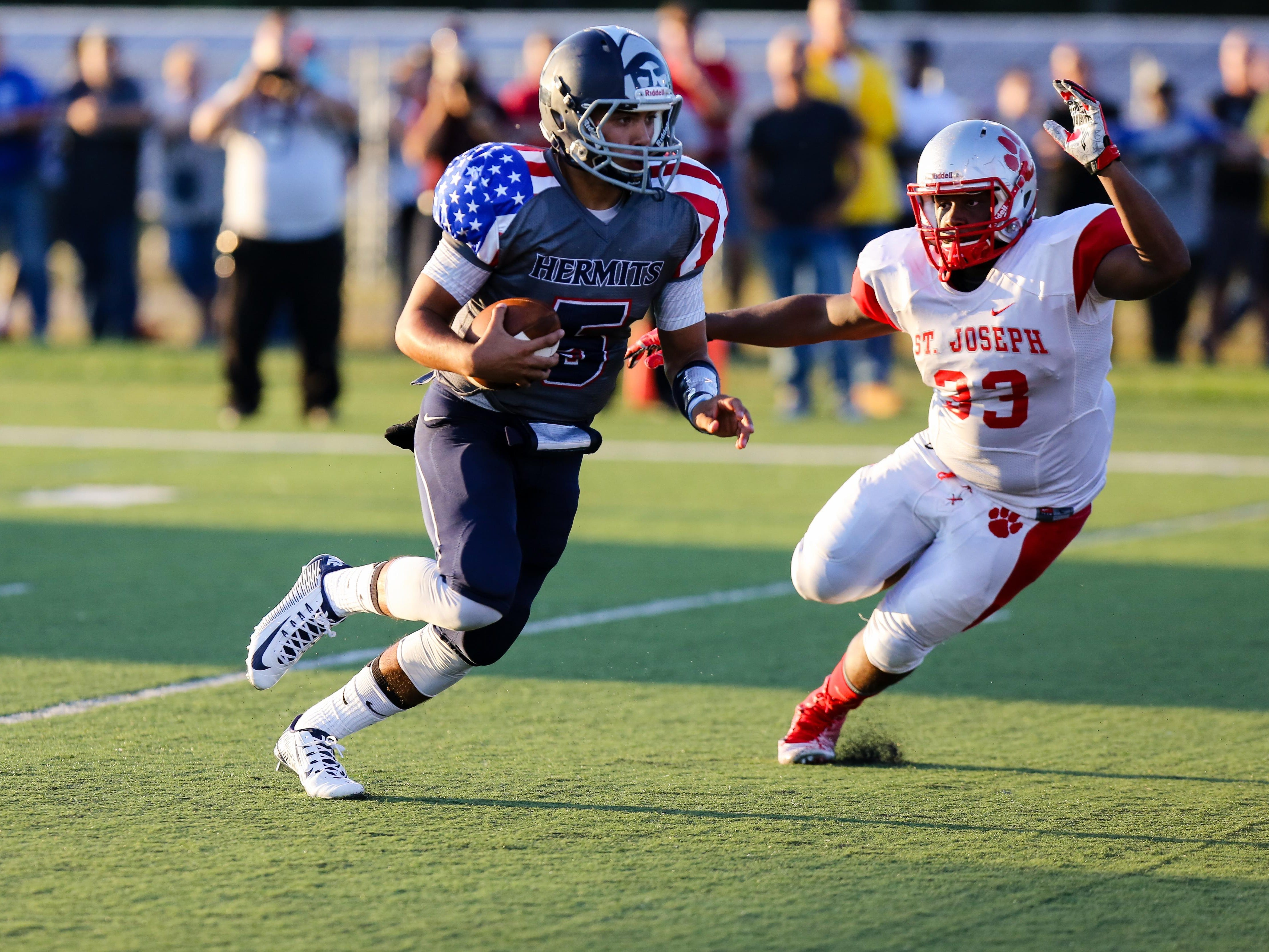 St. Augustine quarterback Jose Tabora (5) looks for open space in the season-opening win against St. Joseph. The Hermits took a 3-0 record into Thursday's game against Ocean City.