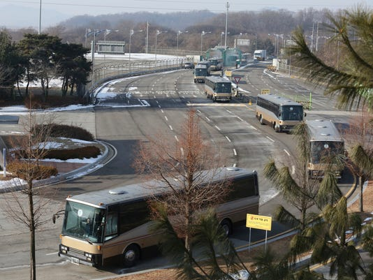 Buses carrying a North Korean delegation arrive at the Korean-transit office near the Demilitarized Zone in Paju, South Korea, Wednesday, Feb. 7, 2018. A North Korean delegation, including members of a state-trained cheering group, arrived in South Korea on Wednesday for the Pyeongchang Winter Olympics. (AP Photo/Ahn Young-joon. Pool)