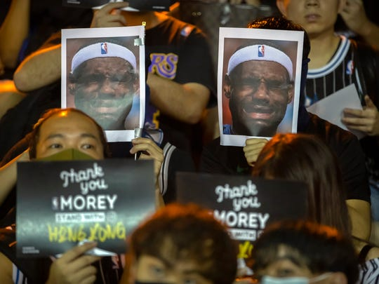Demonstrators hold up photos of LeBron James grimacing during a rally at the Southorn Playground in Hong Kong, Tuesday. Protesters have thrown basketballs at a photo of James and chanted their anger about comments the Lakers star made about free speech.