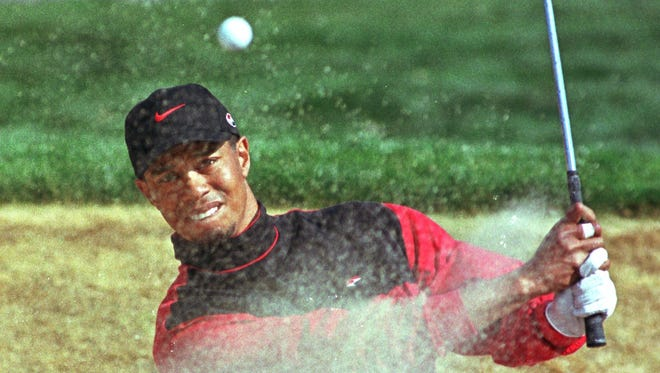 Tiger Woods hits a bunker shot on the third hole during the final round of the Phoenix Open in Scottsdale, Ariz., Sunday, Jan. 31, 1999.