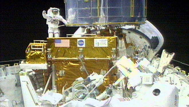 Astronaut John Grunsfeld, right foreground, works to secure equipment to the robot arm as astronaut Steven Smith waves from the Hubble Space Telescope in this televised view from the space shuttle Discovery's cargo bay on Dec. 22, 1999.