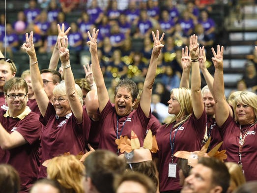 Teachers and staff from Wellington Middle School stand and cheer as they name in called during a district-wide gathering of PSD personnel at the Budweiser Events Center Thursday Aug. 14, 2014, to inspire the PSD employees.