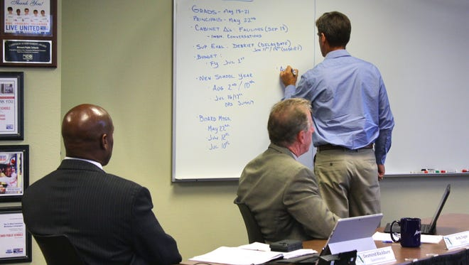 Brevard School Board Chairman John Craig writes out details regarding the search for a new superintendent to replace Desmond Blackburn, left, who is resigning to become CEO of the national nonprofit New Teacher Center.
