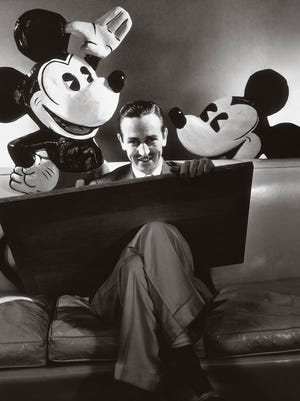 Walt Disney in October 1933 with a drawing board and flanked by representations of his creations, Mickey and Minnie Mouse. The icon's life is chronicled in a new 'American Experience' documentary on PBS.