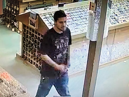 One of two burglars is shown inside The Fly Shop from