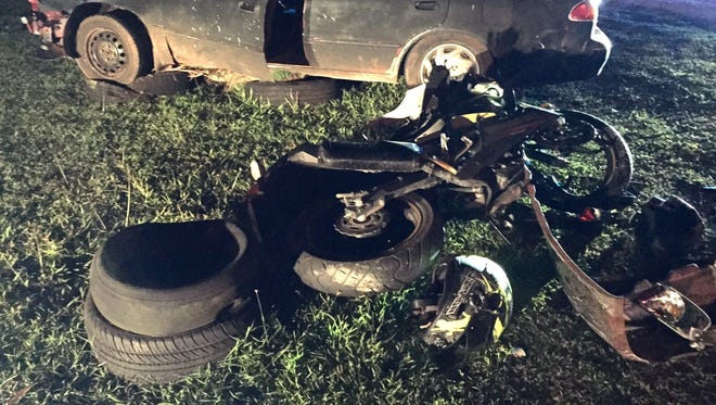 A black Toyota Corolla and a black Kawasaki Ninja sit damaged on the side of the road after a collision in Dededo.