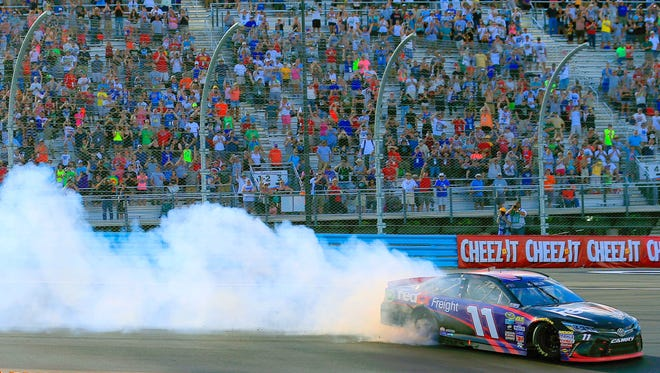 Denny Hamlin, in the No. 11 FedEx Toyota, celebrates with a burnout in front of a packed Turn 1 grandstand after winning the NASCAR Sprint Cup Series Cheez-It 355 at Watkins Glen International in August.