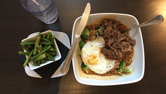 The rice bowl with pulled pork and a side of steamed asparagus at Pure Eatery, located at 221 N. 4th Street in Lafayette.