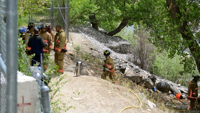 Firefighters investigate a smoldering fire that burned a tent and a few trees along the Truckee River Tuesday morning. The crew had responded to a call of a fire and a possible propane explosion across from the Reno Gazette-Journal.
