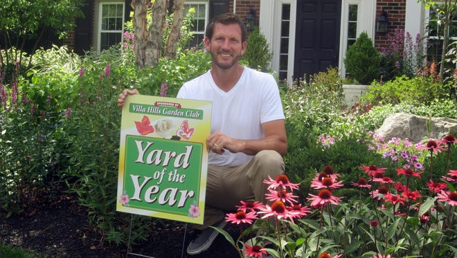 John Winkle displays his Yard of the Year sign in his yard after winning the award from Villa Hills Garden Club.