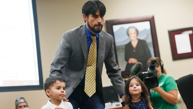 U.S. Air Force combat photographer Steve Otero, center, of Loveland, Colo., guides his 3-year-old twins Dustin, left, and Sophie to the testimony table to voice support for the addition of post-traumatic disorder to the list of ailments eligible for treatment with medical marijuana during a hearing before the Colorado Board of Health Wednesday, July 15, 2015, in Denver. If approved in a vote Wednesday, Colorado would become the 10th state to make PTSD a qualifying condition for medical pot. (AP Photo/David Zalubowski)