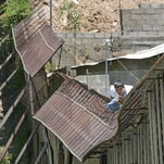 A man climbs over the international border into Nogales, Ariz., from Nogales, Mexico, on May 31, 2006. Since World War I, various border barriers have been pursued between the United States and Mexico.