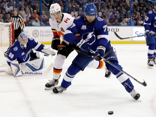 Tampa Bay Lightning defenseman Victor Hedman (77), of Sweden, beats Calgary Flames center Sean Monahan (23) to the puck in front of goaltender Andrei Vasilevskiy (88) during the first period of an NHL hockey game Thursday, Jan. 11, 2018, in Tampa, Fla. (AP Photo/Chris O'Meara)