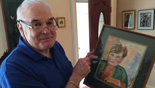 Desmond Murray, of Pittsford, holds a water color portrait of himself as a boy painted by his father, the artist Thomas Murray.
