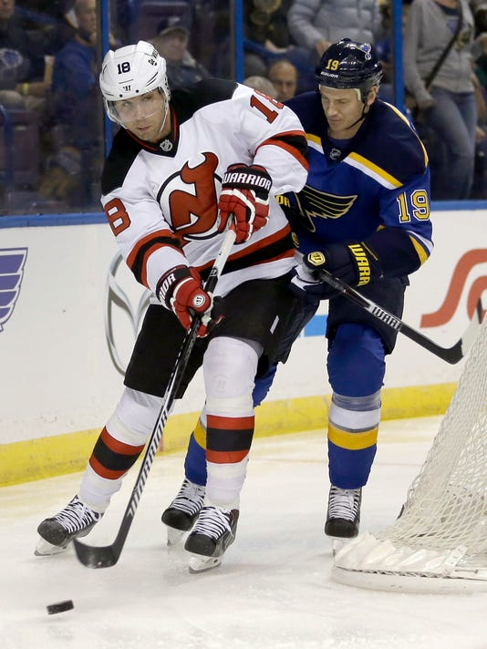 New Jersey Devils' Steve Bernier, left, passes the puck as St. Louis Blues' Jay Bouwmeester defends during the first period of an NHL hockey game Thursday, Nov. 6, 2014, in St. Louis. (AP Photo/Jeff Roberson)
