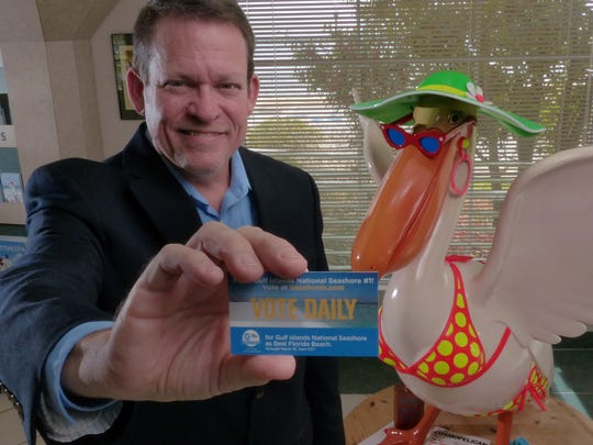 Visit Pensacola President Steve Hayes holds up a card encouraging people to vote Gulf Islands National Seashore as one of the best beaches in Florida.