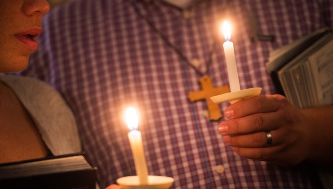 Community supporters light candles during a vigil for journalists Alison Parker and Adam Ward who were killed during a shooting in Moneta, Va., Wednesday, Aug. 26, 2015.