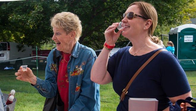 Carol Szymanski, left, and Mary Szymanski, right, taste wine during the festival.