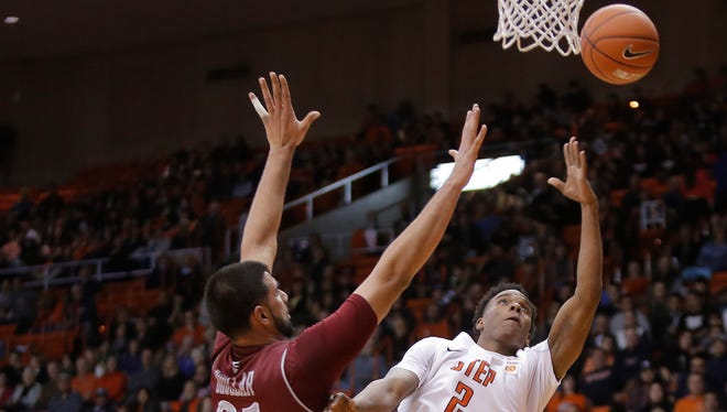 UTEP guard Omega Harris lays up a shot over NMSU center Tanveer Bhullar during their game Saturday at the Don Haskins Center in El Paso.
