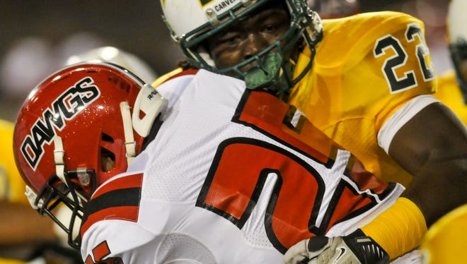 Opelika's Calvin Bryant, left, (25) is tackled by Carver's Daniel McCall (22) during their game at Cramton Bowl on Saturday, Sept. 22, 2012, in Montgomery, Ala.. (Lloyd Gallman, Montgomery Advertiser)