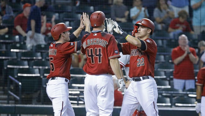 Arizona Diamondbacks' Phil Gosselin (15) and Paul Goldschmidt (44) greet Jake Lamb (22) after his three run home-run against the Philadelphia Phillies  during the first inning of their MLB game Wednesday, June 29, 2016 in Phoenix.