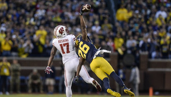 Jourdan Lewis soars for a one-handed interception late in the fourth quarter against Wisconsin.